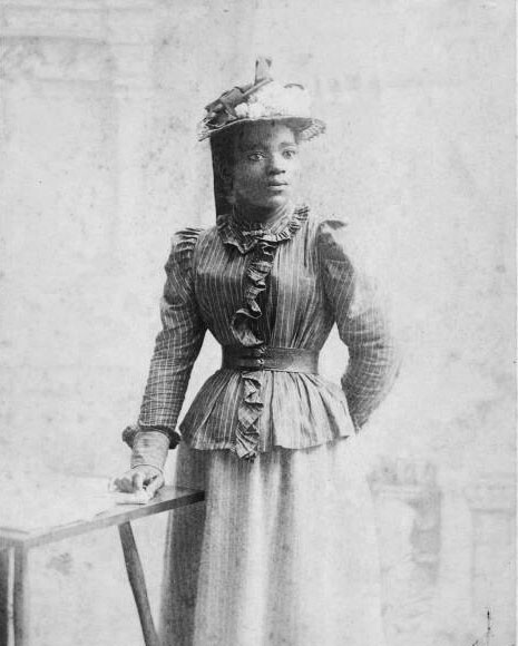 Woman wears 1900s dress and large hat