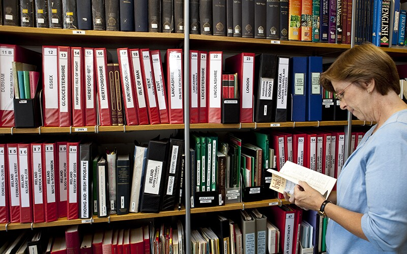 A woman reads a reference book in a library.
